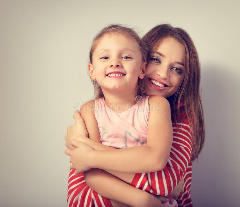 拥抱她的嬉戏的愉快的母亲充满爱的耍笑的做鬼脸的孩子 免版税库存照片