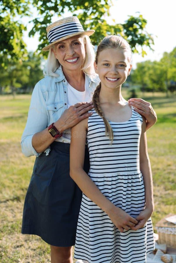 拥抱她的孙女的高兴年长妇女 免版税库存图片