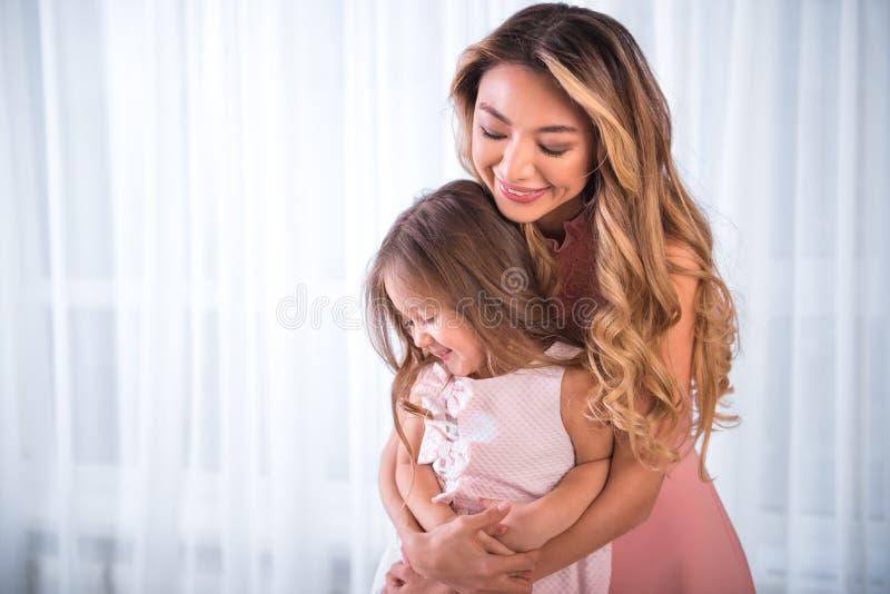 拥抱她的孩子的愉快的asain妇女 免版税图库摄影