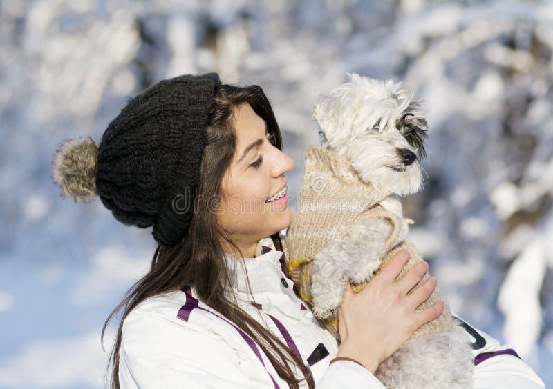 拥抱她的小白色狗的美丽的少妇在冬天森林里 降雪的时间 库存图片