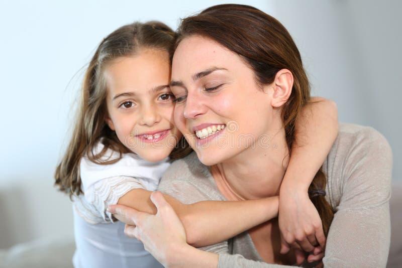 拥抱她的快乐的母亲和她的女儿画象  免版税图库摄影