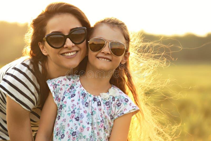 拥抱她的时髦太阳镜的愉快的时尚孩子女孩母亲 免版税库存图片