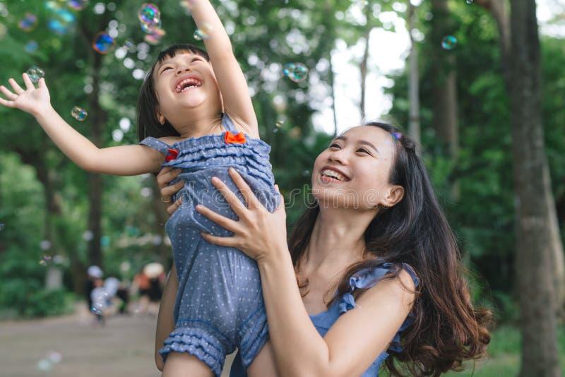 拥抱她的有自然和阳光的,家庭观念的女孩画象妈妈 免版税库存图片
