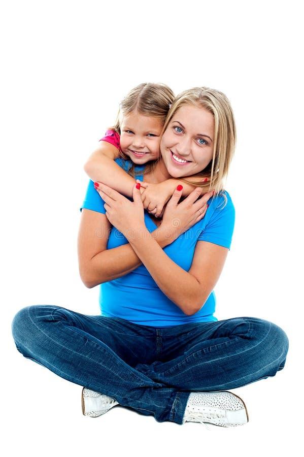 拥抱她的母亲从后面的逗人喜爱的女儿 图库摄影
