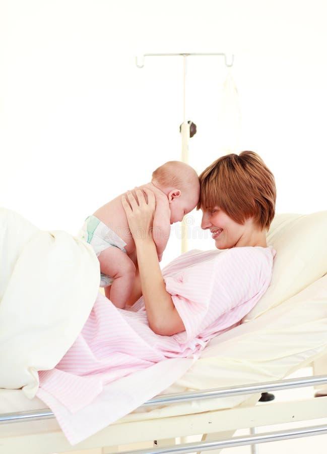 拥抱她的母亲的婴孩新出生 免版税库存图片