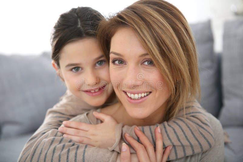 拥抱她的母亲的小女孩画象 免版税库存照片