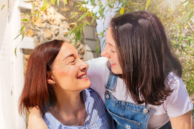拥抱她的母亲的愉快的十几岁的女孩 免版税库存图片
