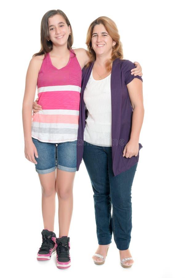 拥抱她的母亲的西班牙十几岁的女孩隔绝在白色 库存照片