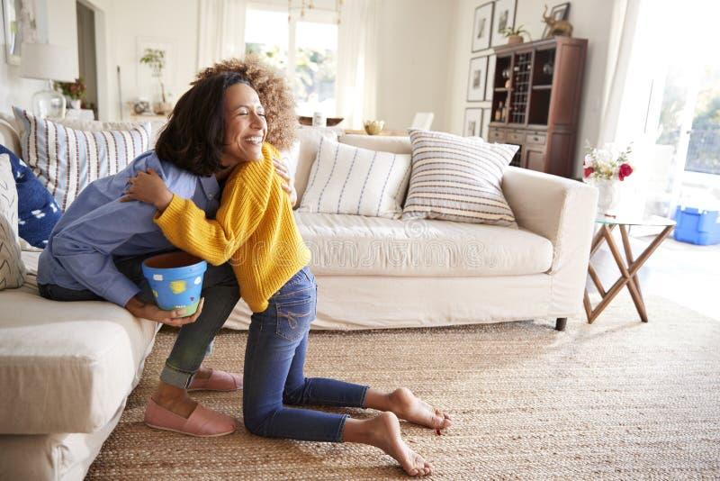 拥抱她的母亲的青春期前的女孩在客厅在给她一件手工制造礼物以后,侧视图 免版税库存图片