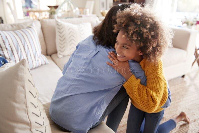 拥抱她的母亲的青春期前的女孩坐沙发在客厅,被举起的,后面看法 库存照片