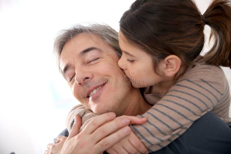 拥抱她的父亲的小女孩 免版税库存照片