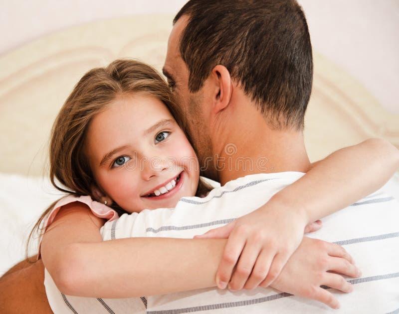 拥抱她的父亲的微笑的愉快的矮小的女儿孩子分享爱 免版税图库摄影