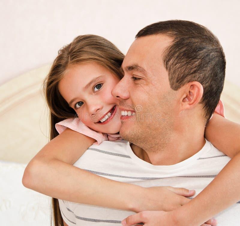 拥抱她的父亲的微笑的愉快的矮小的女儿孩子分享爱 库存照片