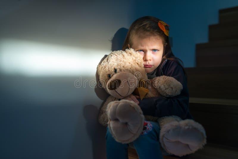 拥抱她的玩具熊的哀伤的小女孩-感到孤独 免版税图库摄影
