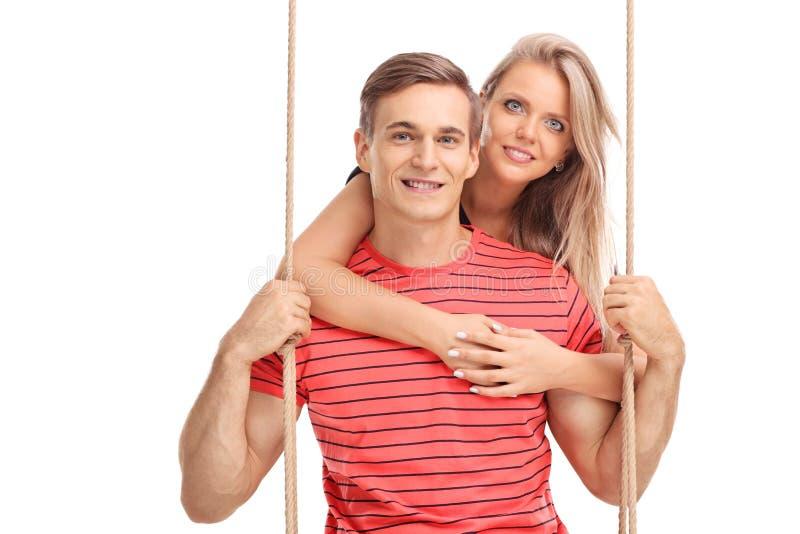 拥抱她的男朋友的年轻白肤金发的女孩 免版税库存照片