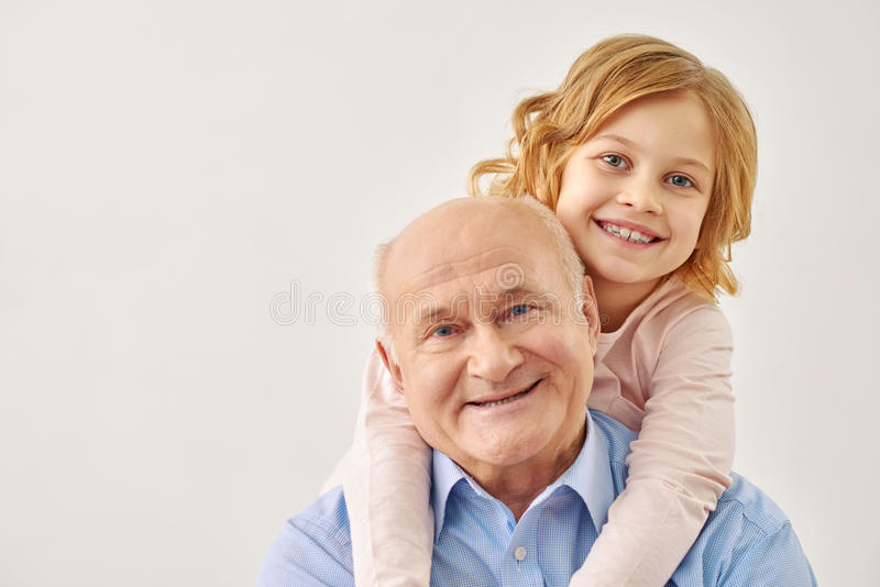 拥抱她的祖父的小孙女 图库摄影