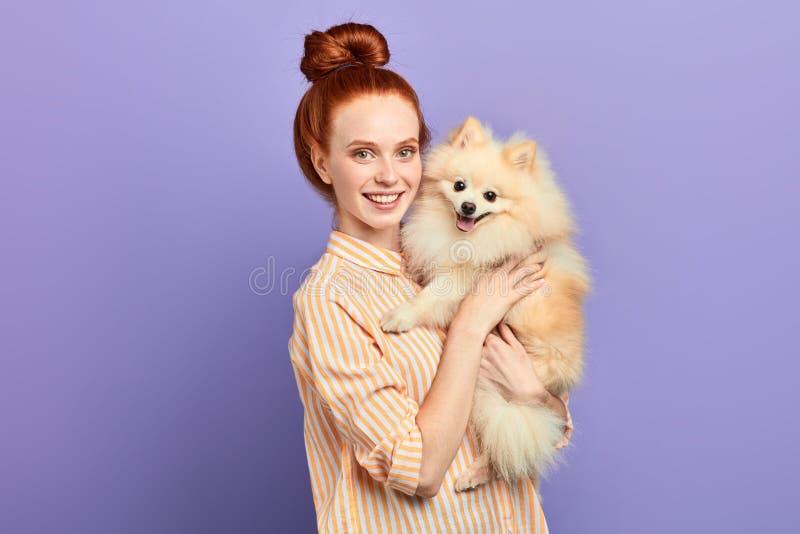 拥抱她的蓬松宠物的迷人的正面女孩 图库摄影