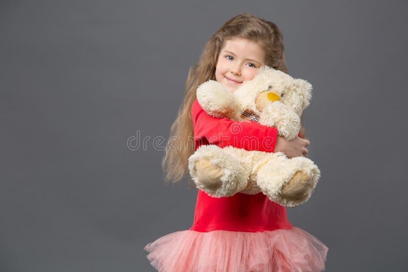 拥抱她的蓬松熊的高兴逗人喜爱的女孩 免版税库存照片