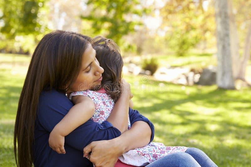 拥抱她的年轻女儿的混合的族种亚裔妈咪在公园 库存图片