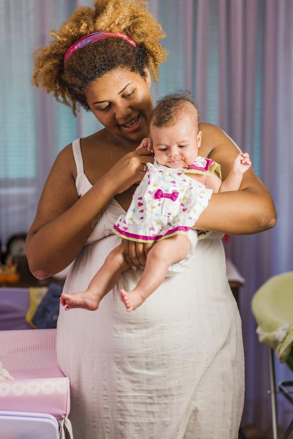 拥抱她的婴孩的非裔美国人的母亲 免版税库存照片