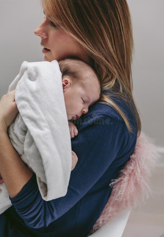 拥抱她睡觉的女婴的母亲 库存照片