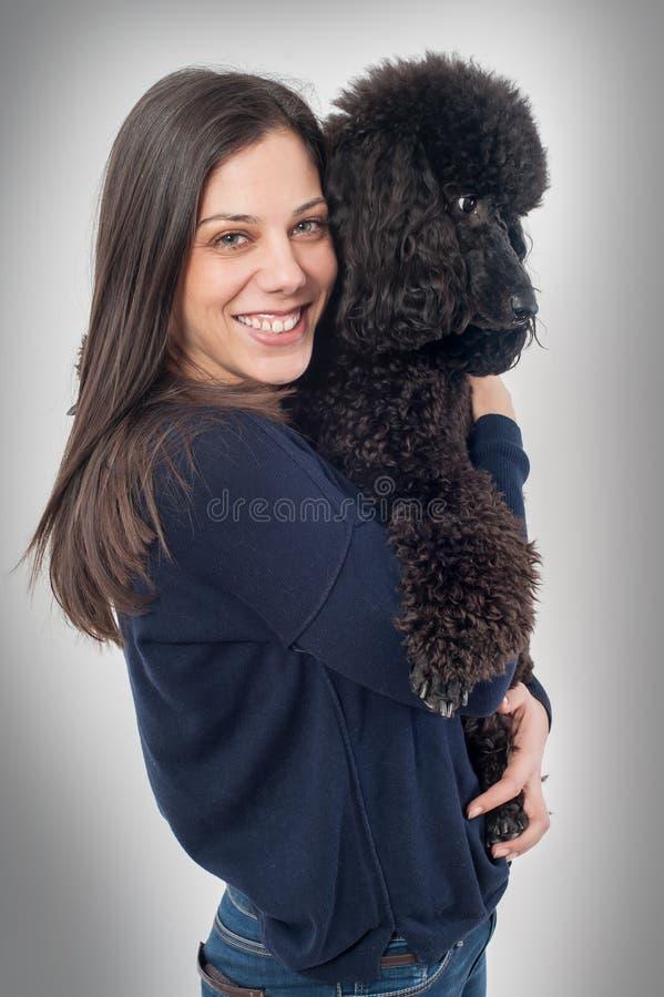 拥抱她美丽的狗的一个美丽的少妇的画象 免版税库存照片