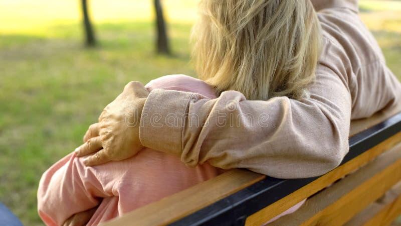 拥抱妇女的老人坐在公园,浪漫关系,统一性 库存图片