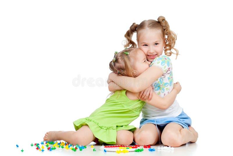 拥抱姐妹的女孩使用和 免版税库存照片