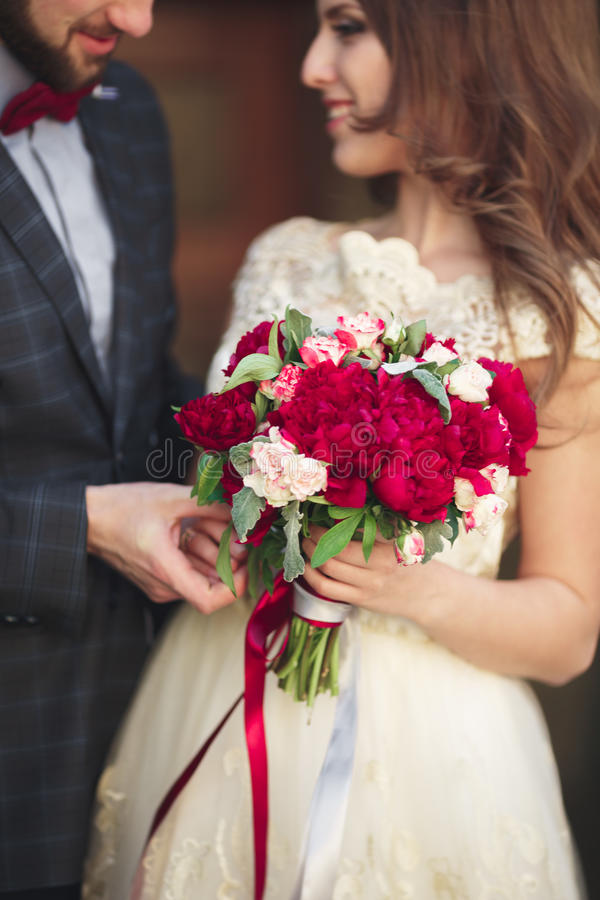 拥抱婚礼的夫妇,拿着花的花束新娘在她的手,新郎拥抱上 库存照片