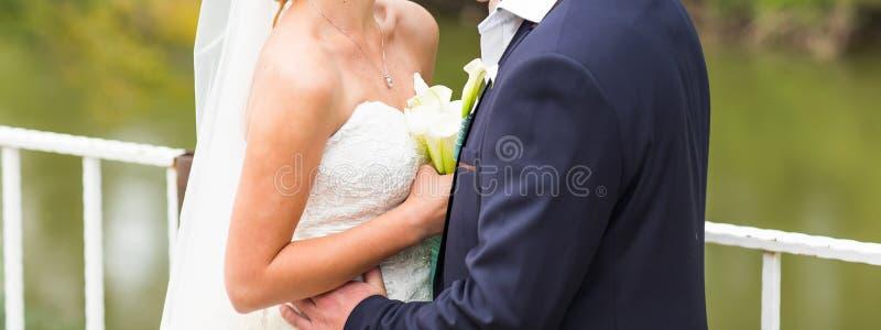 拥抱婚礼的夫妇,拿着花的花束新娘,拥抱她的新郎 免版税图库摄影