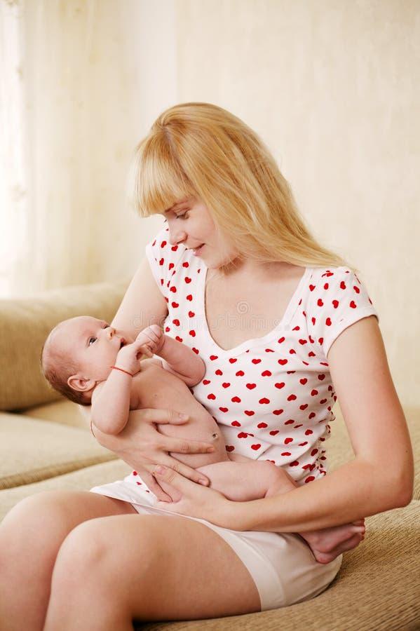 拥抱婴孩的新母亲 免版税库存图片