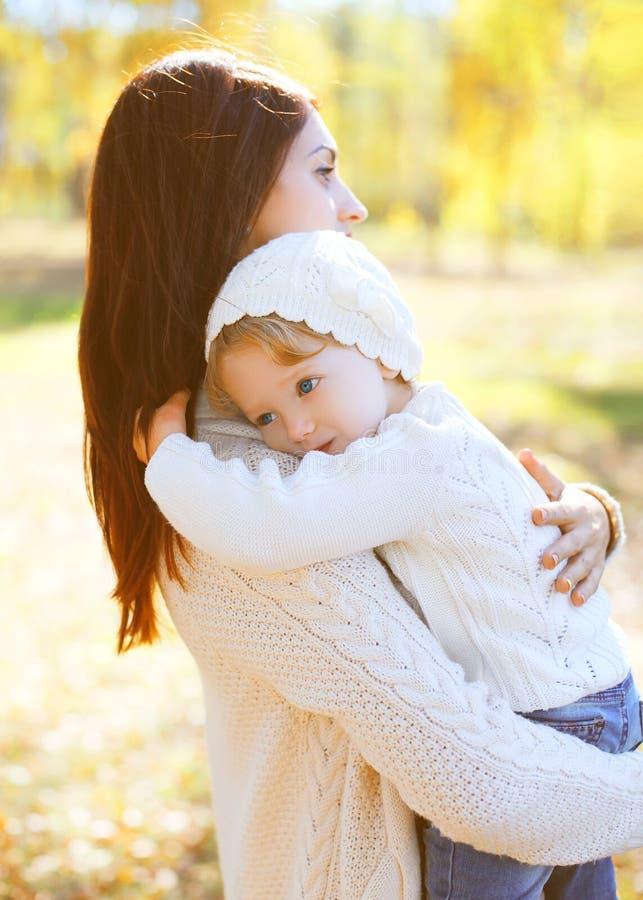 拥抱孩子的愉快的爱恋的母亲在秋天天 免版税库存照片