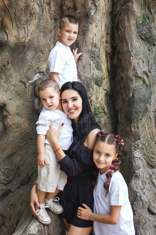 拥抱孩子的母亲在树附近 库存照片