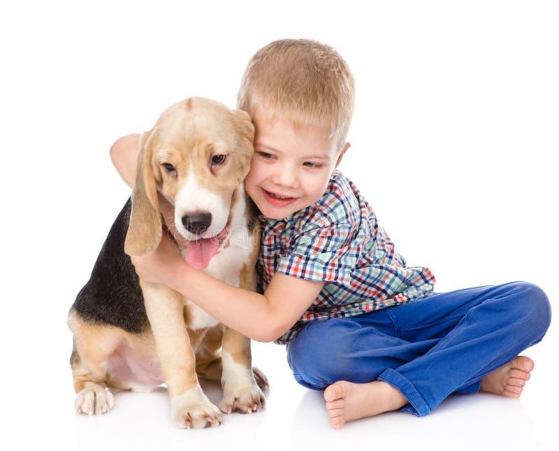 拥抱小猎犬小狗的小男孩 背景查出的白色 免版税库存照片