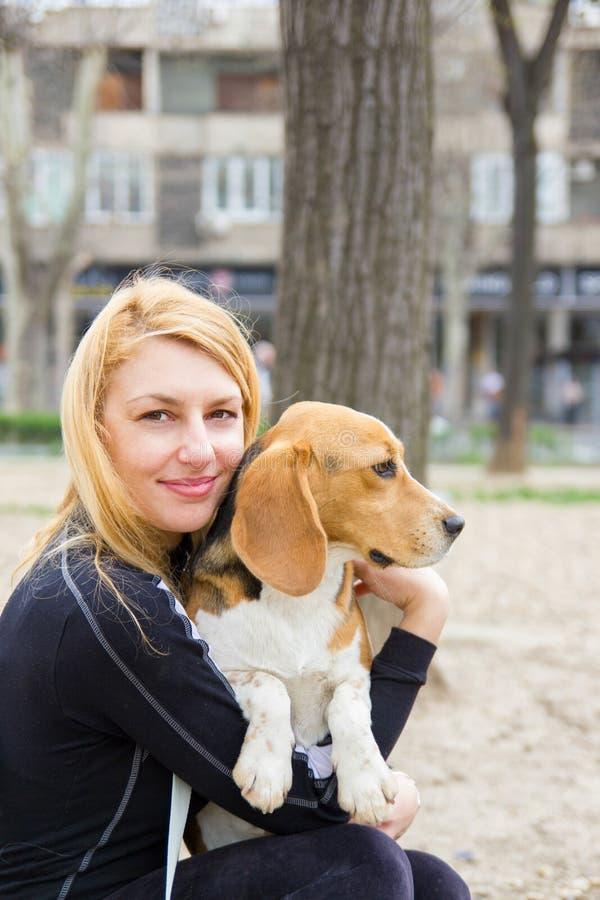 拥抱小猎犬狗的女孩在公园 图库摄影