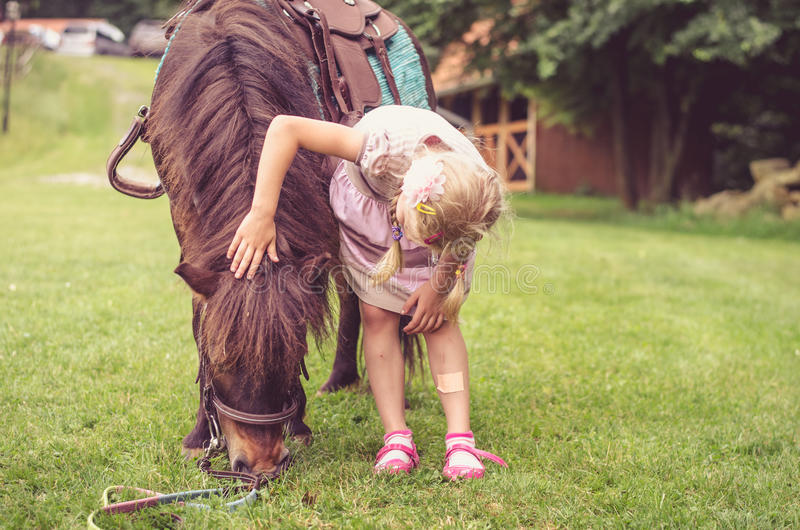 拥抱小的棕色小马的孩子 库存照片
