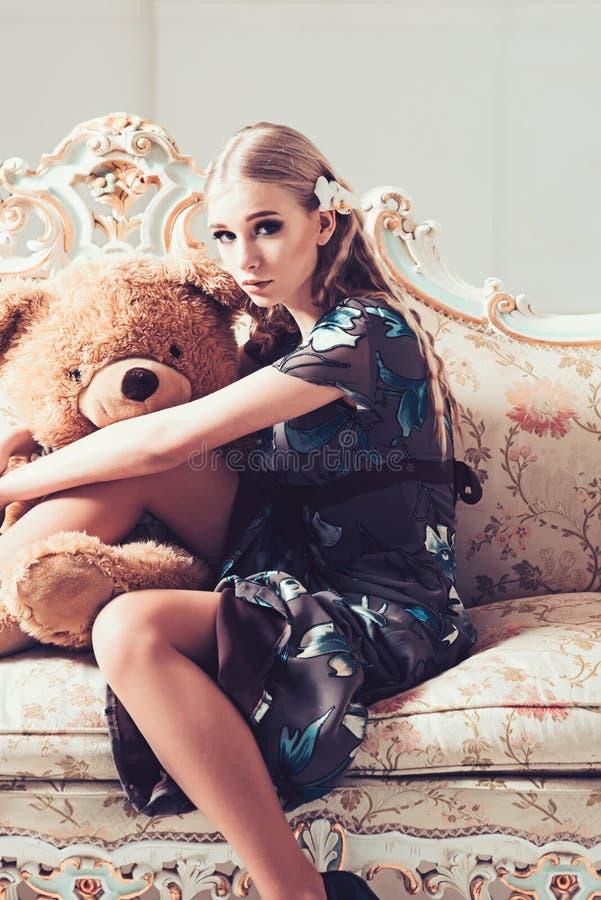 拥抱巨大的玩具熊的可爱的白肤金发的女孩,当坐减速火箭的沙发时 用花装饰的灰色礼服的亭亭玉立的妇女在她的屋子里 库存图片