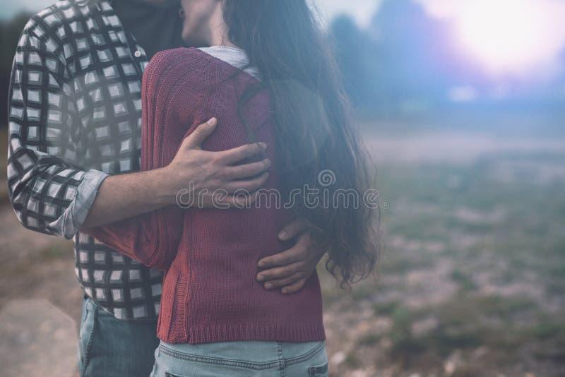 拥抱年轻爱恋的夫妇户外 免版税库存图片