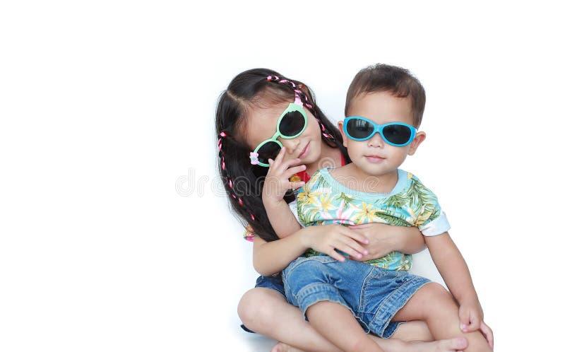 拥抱弟弟的画象小亚裔姐妹戴在白色背景和太阳镜隔绝的花夏天礼服 免版税库存图片
