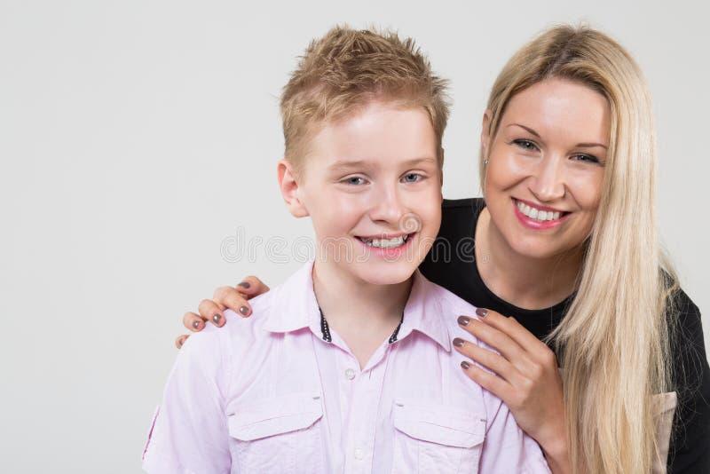 拥抱微笑的儿子的愉快的母亲 免版税库存图片