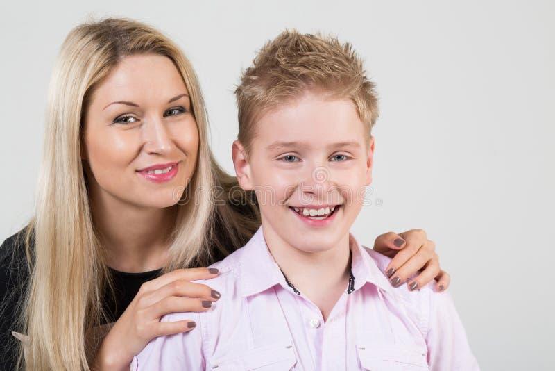 拥抱微笑的儿子的愉快的母亲 免版税库存照片