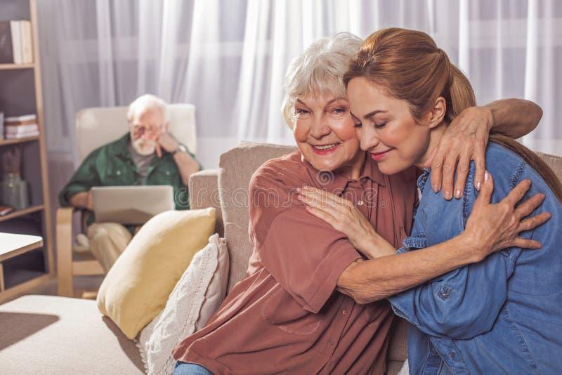 拥抱微笑的妇女的快乐的老母亲 库存图片