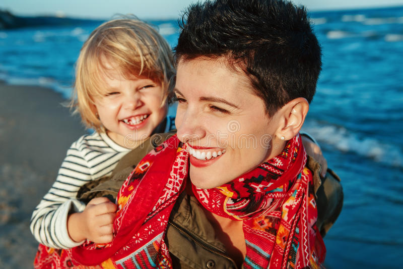 拥抱微笑的笑的白白种人母亲和女儿女婴画象演奏跑在海洋海海滩 免版税库存图片