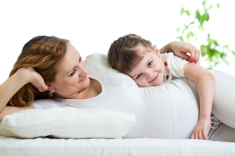 拥抱怀孕的妈妈的愉快的孩子 免版税库存图片