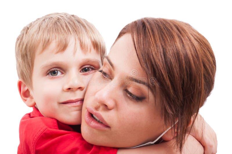 拥抱愉快的儿子的防护母亲 免版税库存图片