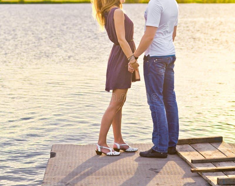 拥抱愉快的夫妇,当站立在银行时 免版税库存图片