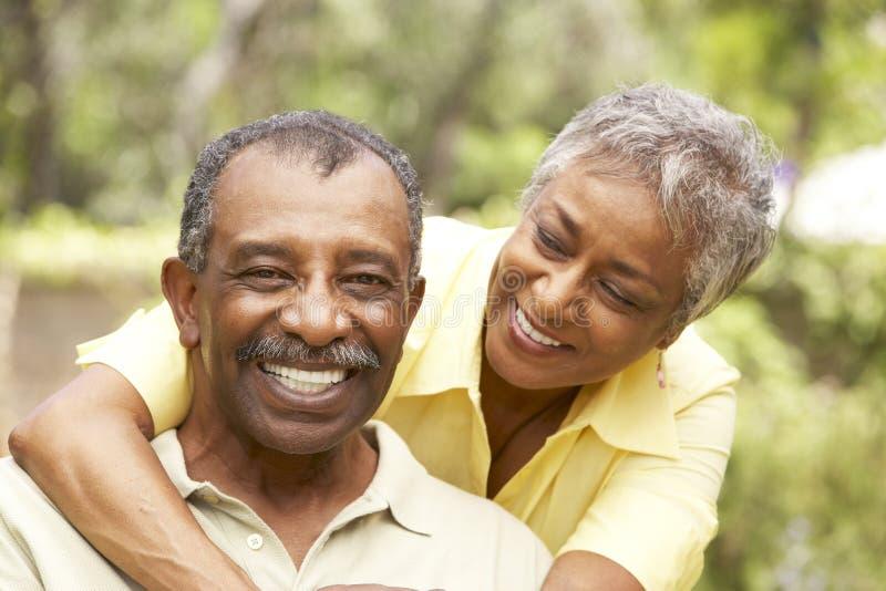 拥抱户外前辈的夫妇 免版税库存照片