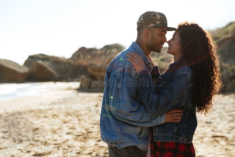 拥抱户外在海滩的愉快的非洲爱恋的夫妇 库存图片
