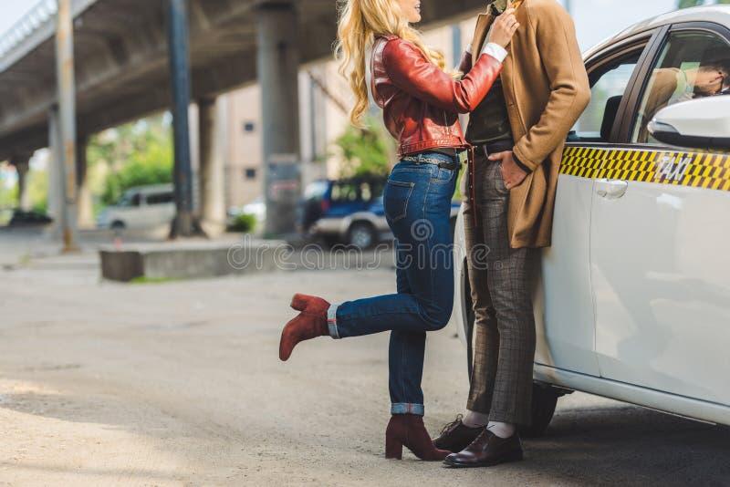拥抱时髦的年轻的夫妇播种的射击,当一起时站立 免版税库存照片