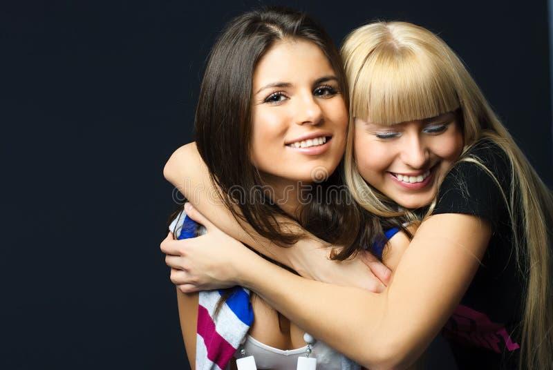 拥抱朋友愉快的二个年轻人 库存图片